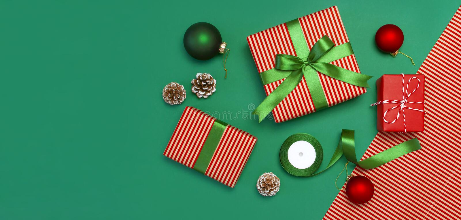 Gift boxes, Christmas balls, toys, fir cones, ribbon on green background. Festive, congratulation, New Year Christmas presents Xma stock photo