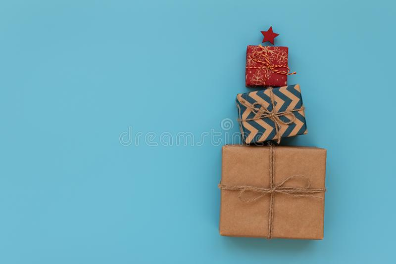 Gift boxes in Christmas fir tree shape on blue background. Flat lay. Christmasr gift packing. Christmas or New Year celebration stock photography