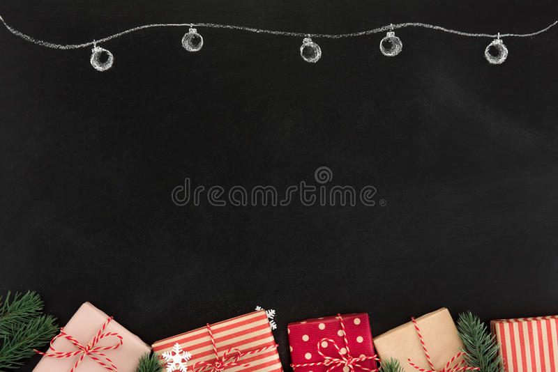 Gift boxes and Christmas ornaments, border design, on blackboard stock photography