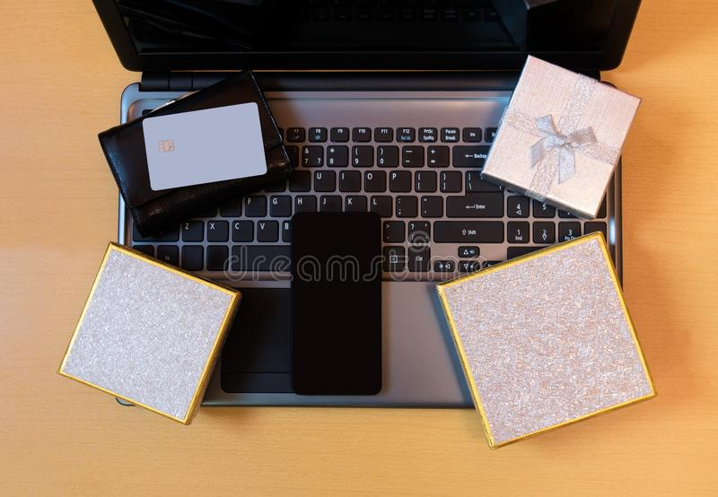 Gift boxes, credit card and smartphone on laptop keyboard. stock photo