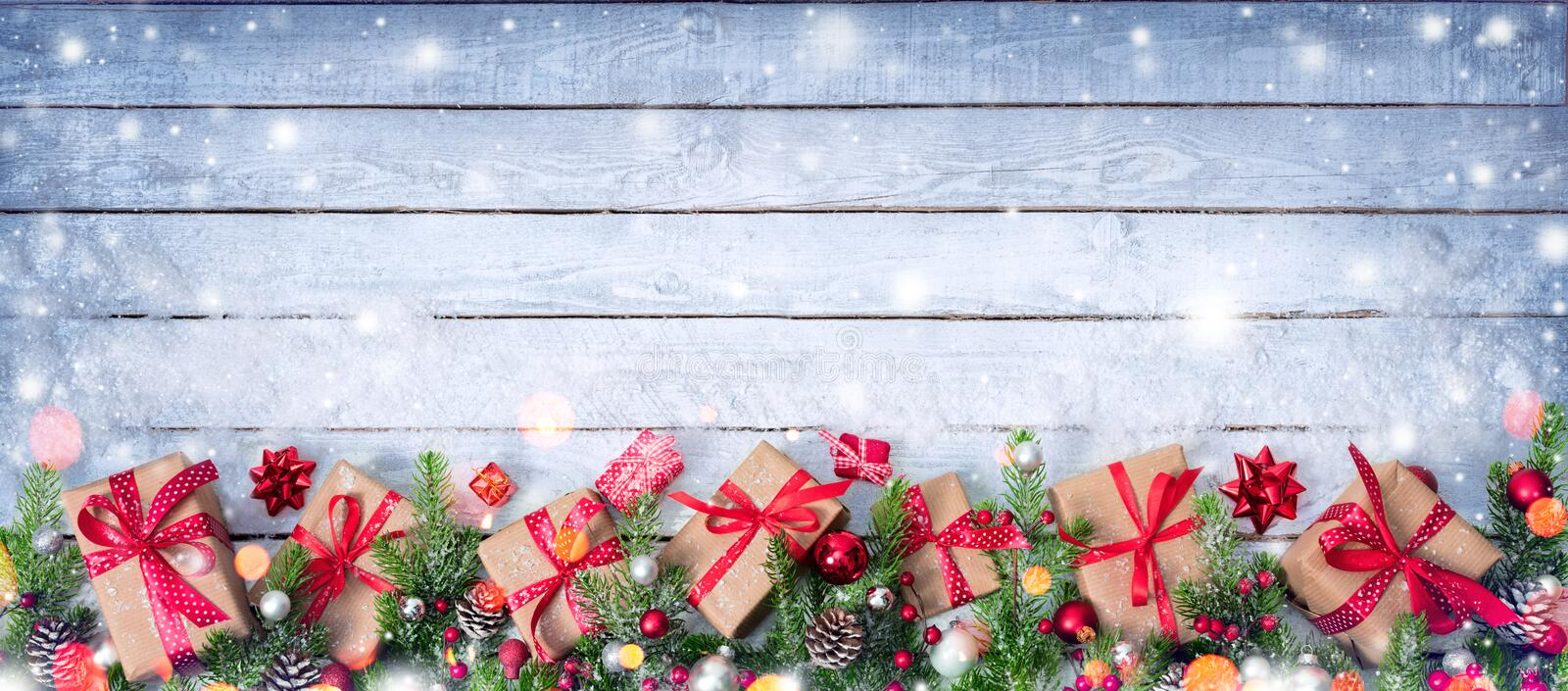 Gift Boxes And Decorated Fir Branches On Snowy Table stock images
