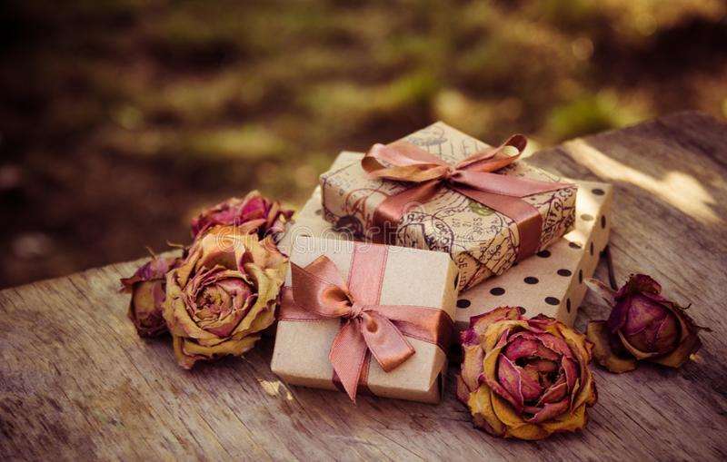Gift boxes and dry roses. Dried flowers and craft gift box. stack of gifts and dried flowers. stock photo