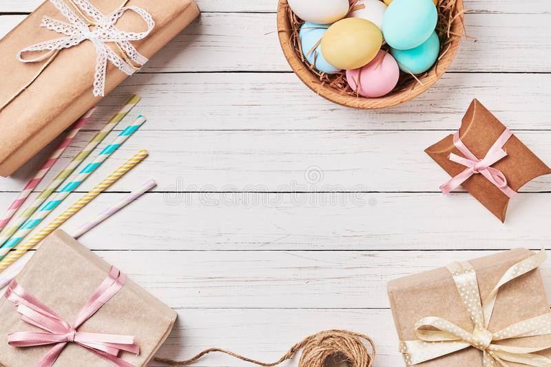 Gift boxes, easter eggs and decorations on a white wooden background, top view with copy space royalty free stock photos