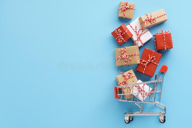 Gift boxes flying out of a shopping cart on black background. Christmas or Black Friday sale concept. Flat lay, full, trolley, advent, advertising, basket royalty free stock images