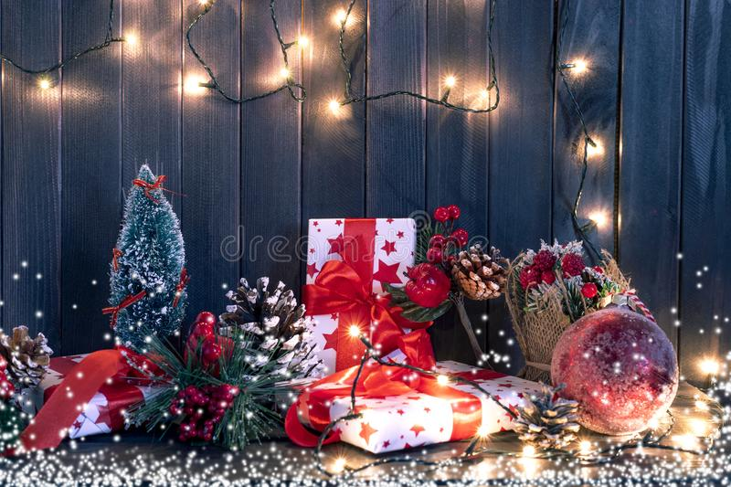 Gift boxes and garland lights over old wooden background. Christmas and new year concept royalty free stock images