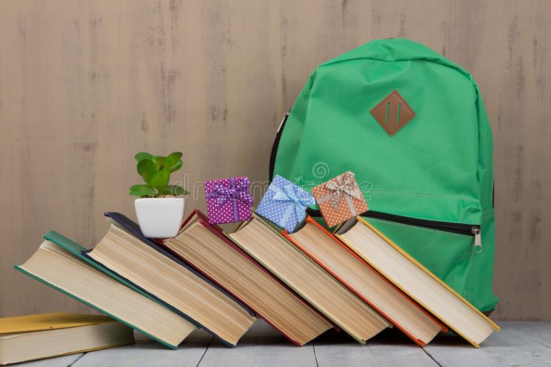Gift boxes, backpack and heap of colorful books royalty free stock photos