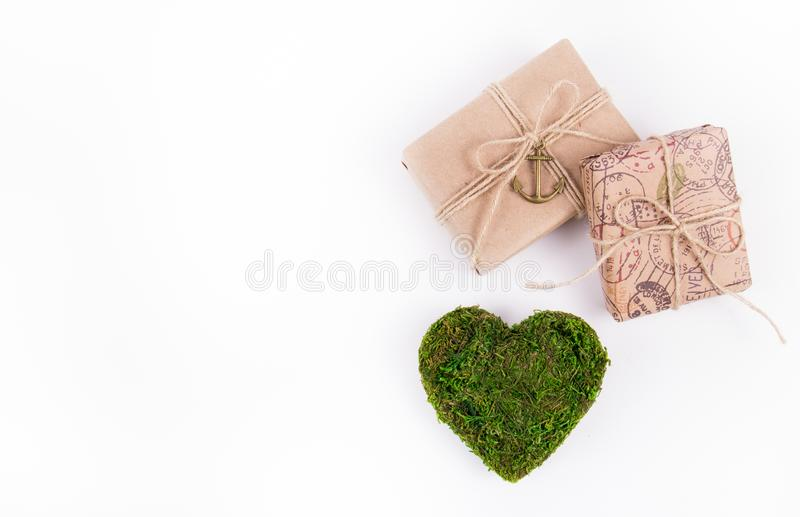 Gift boxes and a green heart. Valentine`s moss. Postcard of valentine from natural materials. royalty free stock photos