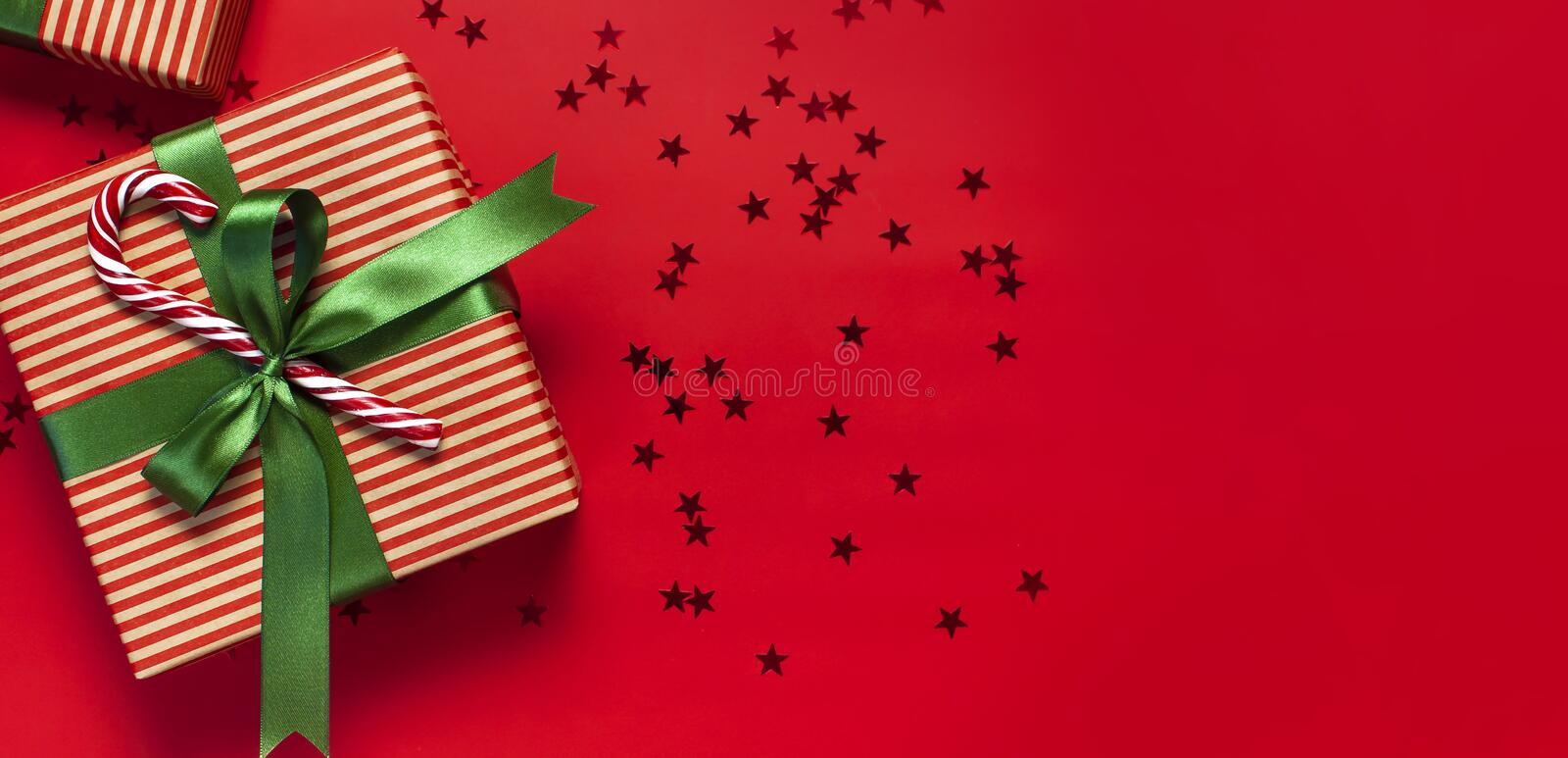 Gift boxes with green ribbon, Candy Cane, glitter confetti form of stars on red background top view flat lay. Holiday concept, new. Gift boxes with green ribbon stock photography