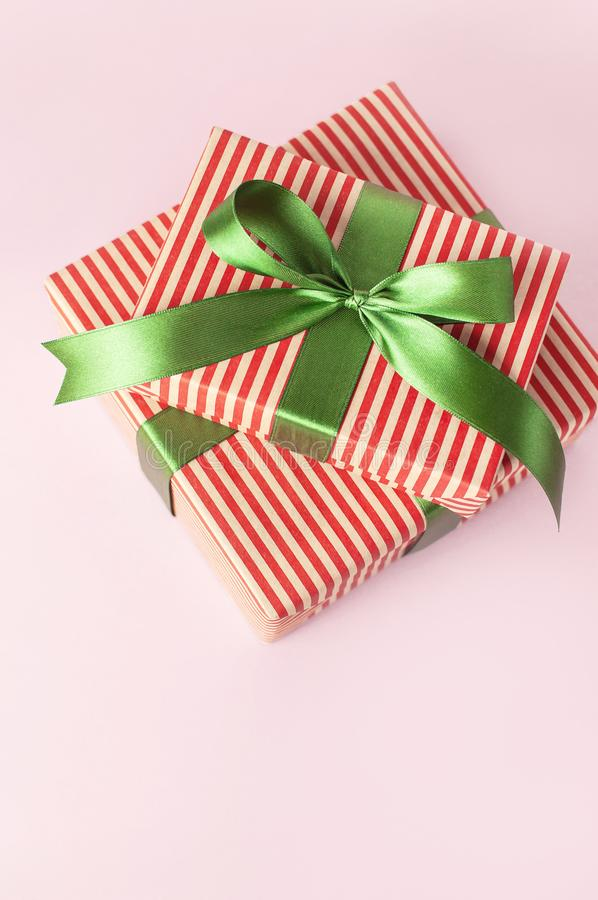 Gift boxes with green ribbon on pink background top view flat lay. Holiday concept, new year or Christmas gift box, presents Xmas stock photos