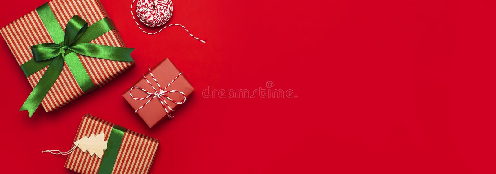 Gift boxes with green ribbon on red background top view flat lay. Holiday concept, new year or Christmas gift box, presents Xmas h stock images