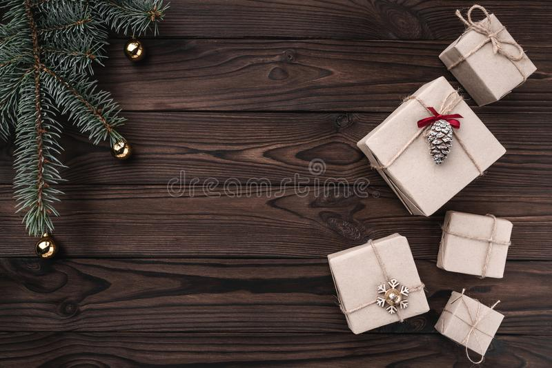Gift boxes over dark wooden background. Top view. Fir tree with baubles, space for text stock photography