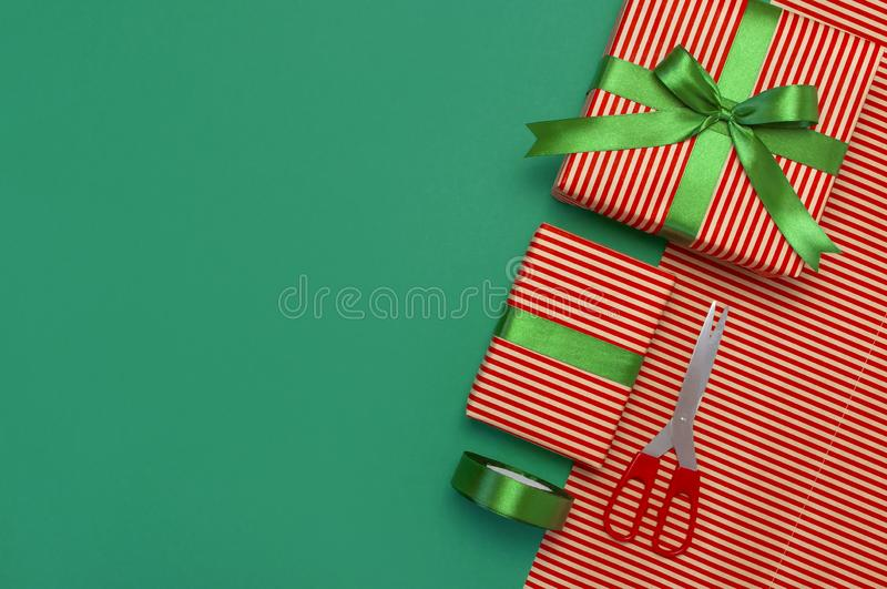Gift boxes, packing paper, scissors, ribbon on green background. Festive background, congratulation, gift wrapping, Christmas and royalty free stock image