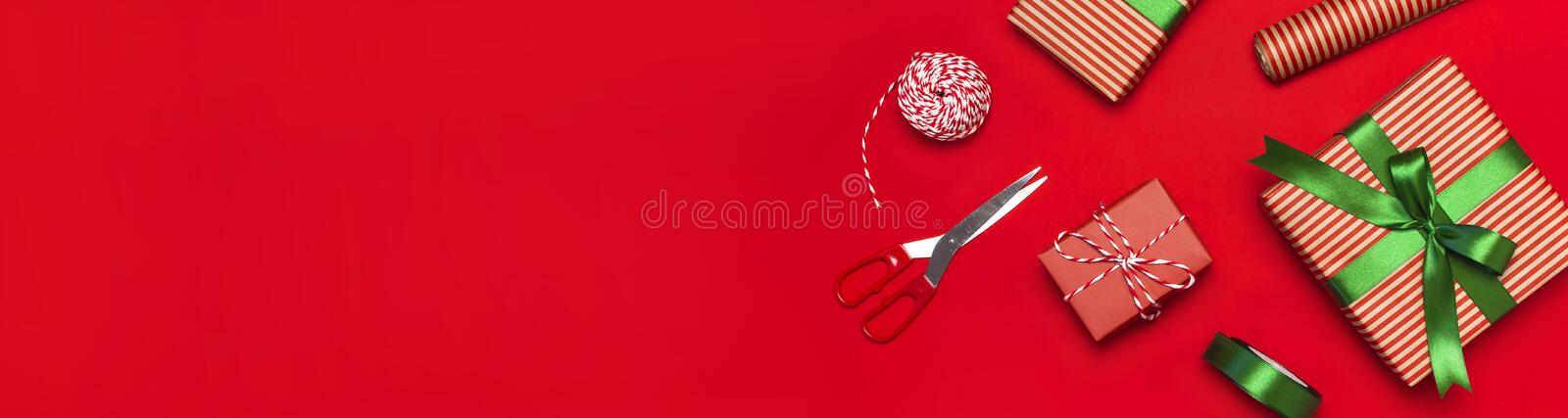 Gift boxes, packing paper, scissors, ribbon on red background. Festive background, congratulation, gift wrapping, Christmas and ne royalty free stock images
