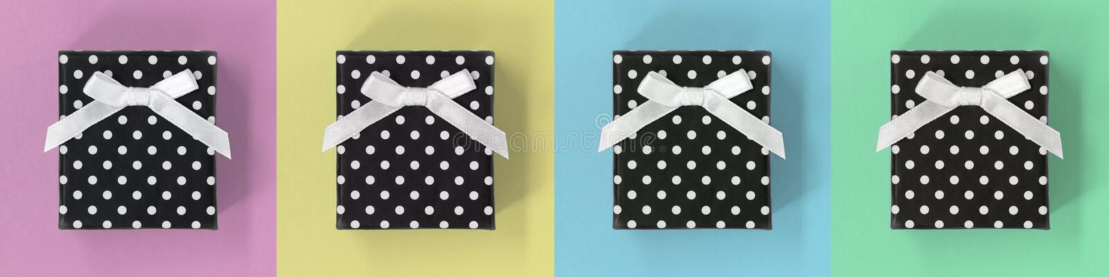 Gift boxes banner, on pastel multicoloured squares. Four black gift boxes with polka dots and bows, on a pastel multicoloured banner, with square backgrounds royalty free stock photos