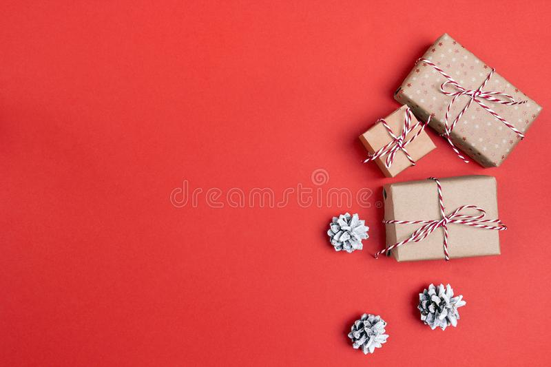 Gift boxes with pine cones on red background and space for text. Christmas background. Top view royalty free stock photo