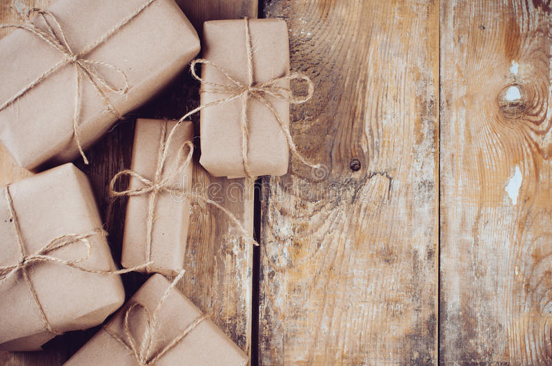 Gift boxes, postal parcels on wooden board. Several gift boxes, postal parcels wrapped in brown kraft paper tied with a rope on a wooden board stock image