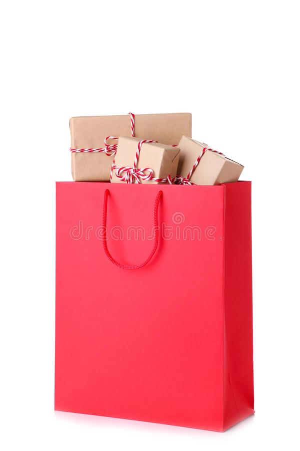 Gift boxes in red paper bag isolated on white background, shopping concept stock images