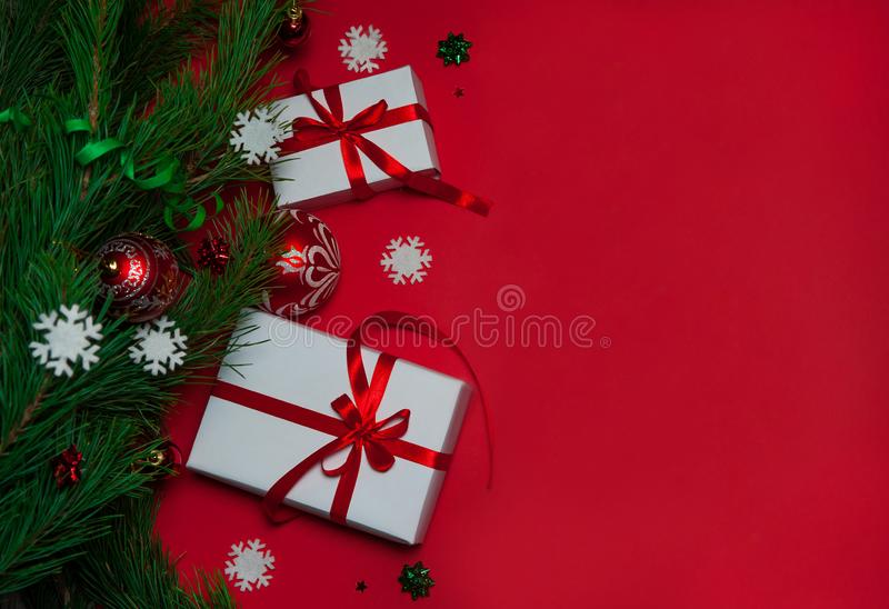Gift boxes with red ribbons lie under the Christmas tree on a red background. Balls, serpentine and white snowflakes. Christmas composition. Gift boxes with red stock images