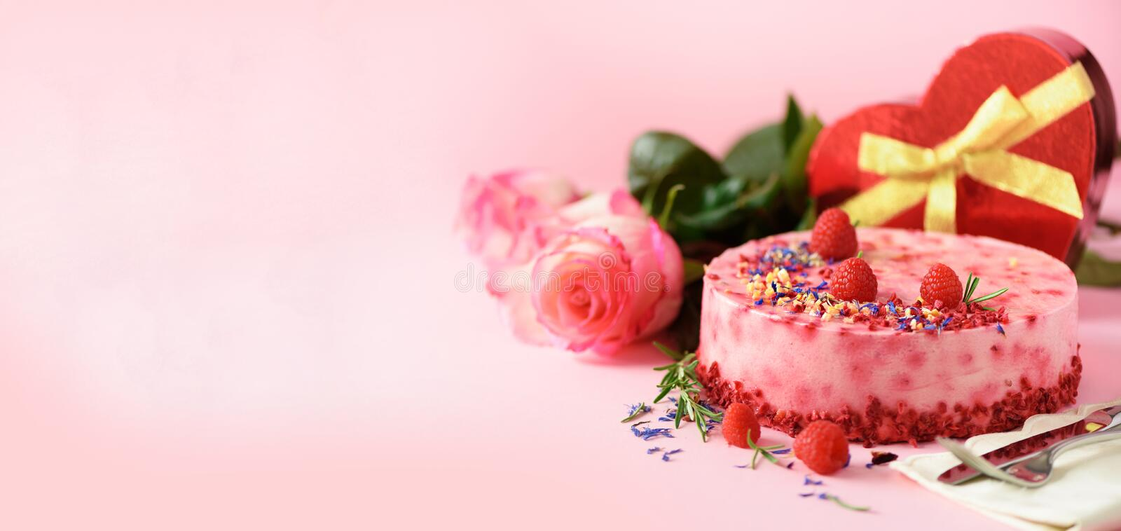 Gift boxes in shape of heart, roses, raspberry cake with fresh berries, rosemary and dry flowers on pink background. Banner, copy royalty free stock images