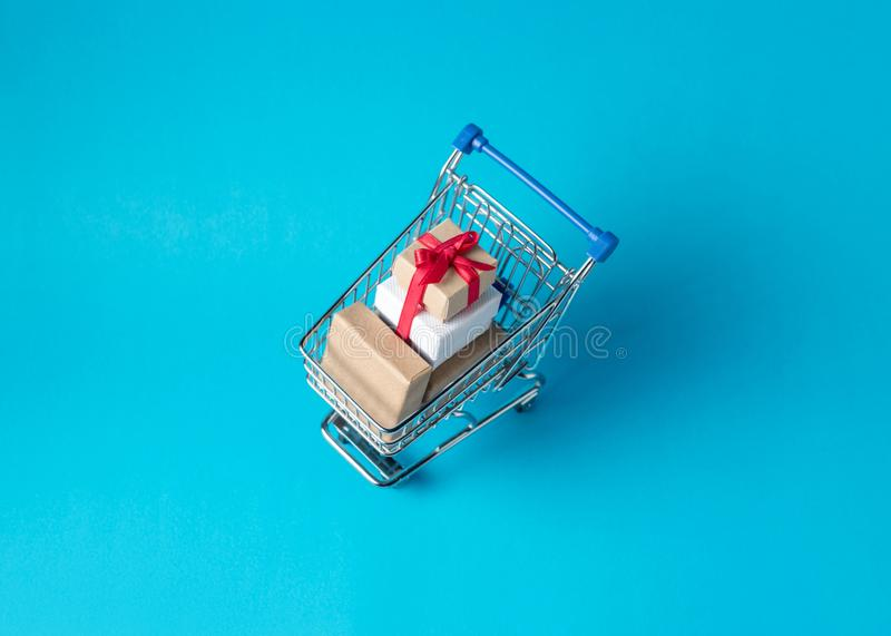 Gift boxes in shopping cart on blue background. Minimal sale concept. royalty free stock photos
