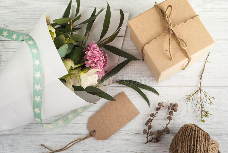 Gift Boxes with Tag. Wooden background, bouqet of flowers royalty free stock photography