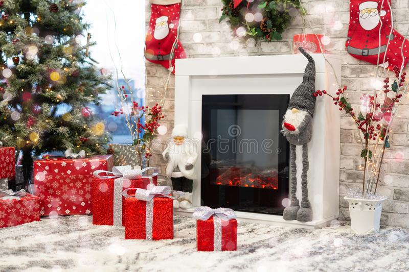 Gift boxes under Christmas tree, New Year home decorations, red wrapping Santa presents, fir tree decorated, beautiful bokeh of stock photography