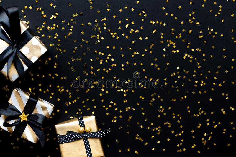 Gift boxes in various gold pattern wrapping papers over star shaped golden sequins on a black background stock image