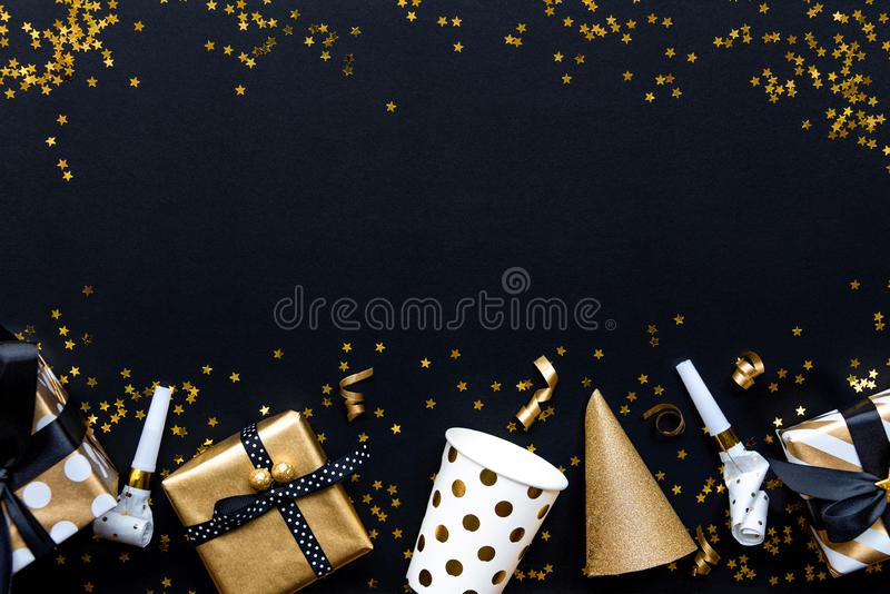 Gift boxes in various gold pattern wrapping papers and party accessories over star shaped golden sequins on a black background royalty free stock photos