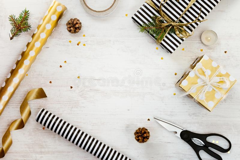 Gift boxes wrapped in black and white striped and goden dotted paper with, pine, cones, candle and wrapping materials on a white w. Ood old background. Christmas royalty free stock photo