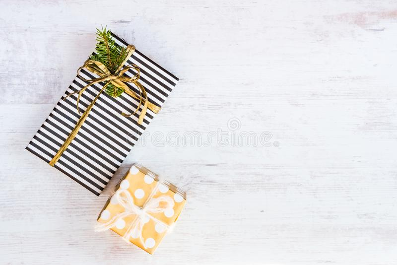 Gift boxes wrapped in black and white striped and golden dotted paper on a white wood background. Christmas presents. Empty space. royalty free stock photography
