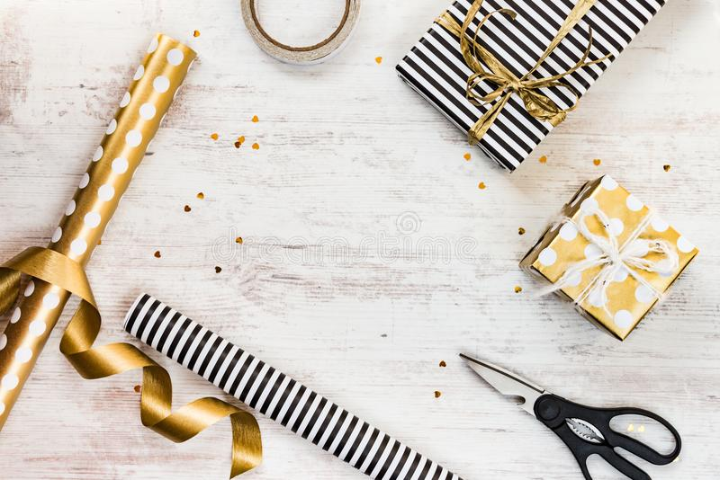Gift boxes wrapped in black and white striped and golden dotted paper and wrapping materials on a white wood old background. Empty. Space stock photo