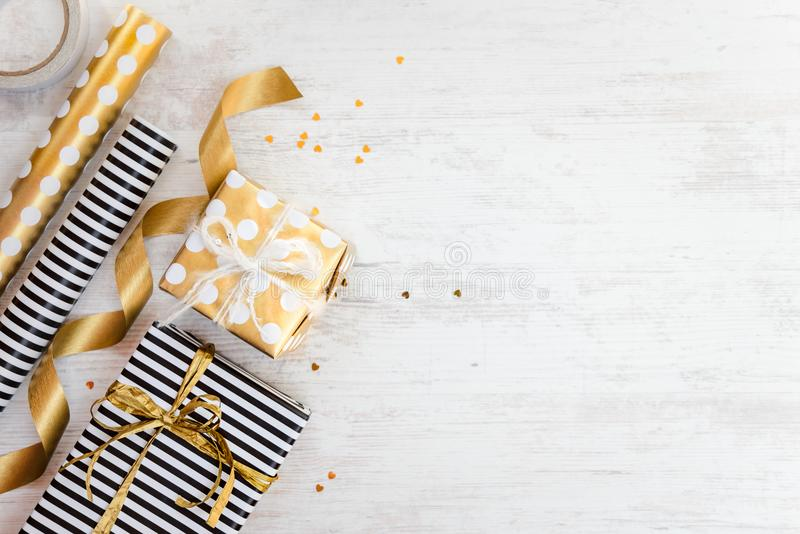 Gift boxes wrapped in black and white striped and golden dotted paper and wrapping materials on a white wood old background. Empty royalty free stock photography