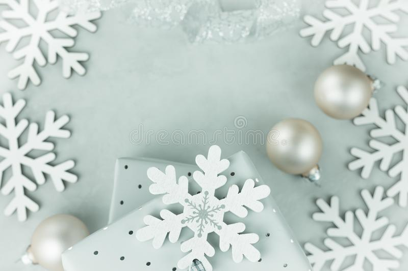 Gift boxes wrapped in silver paper. Curled silver ribbon. Christmas baubles, snow flakes arranged in frame. Copy space for text. stock photos