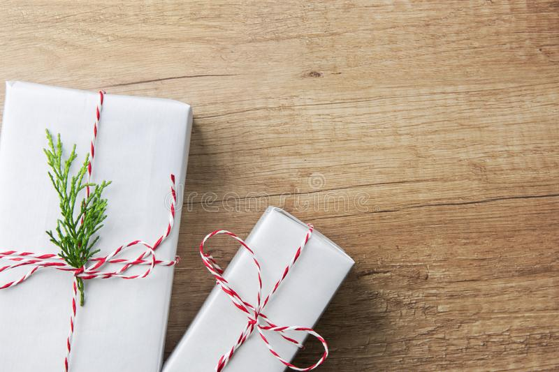 Gift boxes wrapped in white paper tied with striped red ribbon twig of green juniper on brown wood background. Christmas New Years stock photo