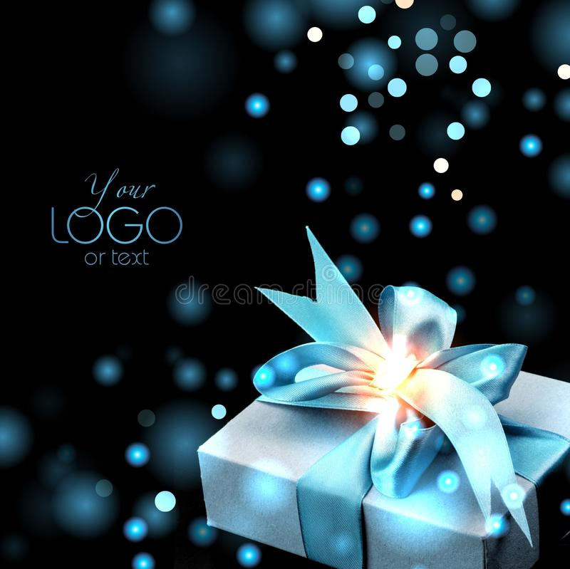 A gift with a bright blue bow on a dark background with glitter. A beautiful gift box with silk bow on a dark background. There are a lot of sparkles and royalty free stock photography
