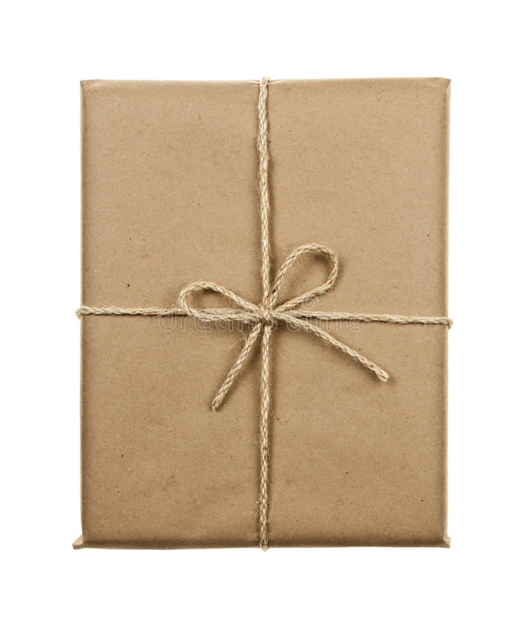 Gift in brown paper tied with string. Gift package in brown paper wrapper tied with twine isolated on white background royalty free stock photo