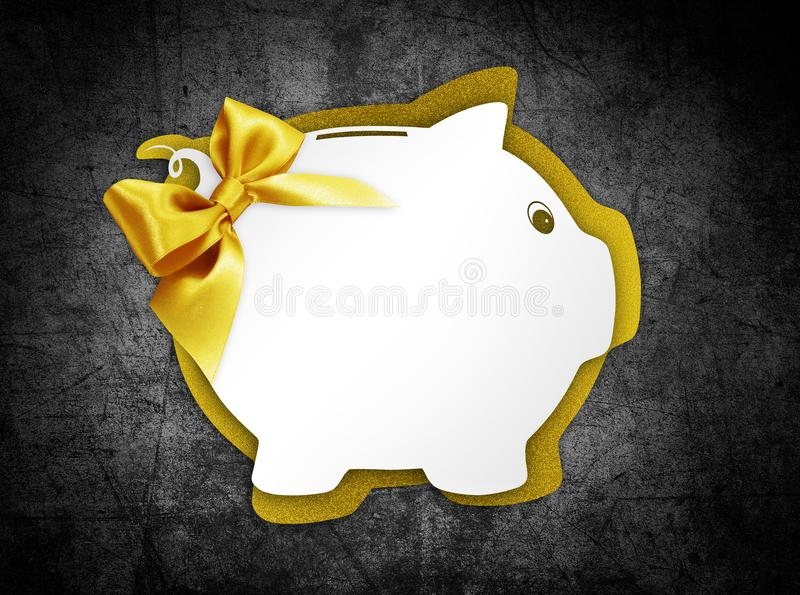 Gift card label in the shape of a piggy bank with golden ribbon. Glitter bow isolated on black background royalty free stock image