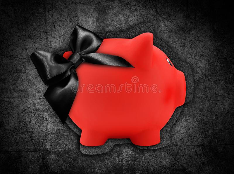 Gift card label in the shape of a red piggy bank with black glitter ribbon bow isolated on black background royalty free stock photography