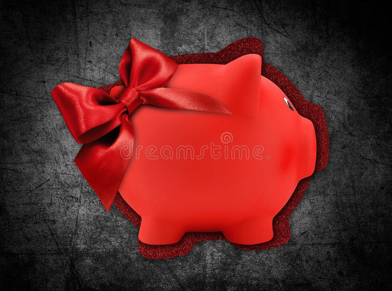 Gift card label in the shape of a red piggy bank with red glitter ribbon bow isolated on black background stock photo