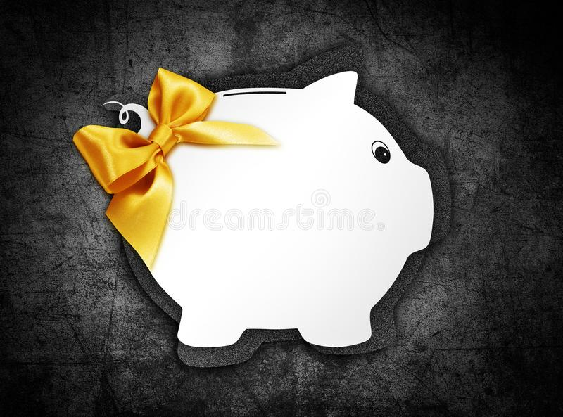 Gift card label in the shape of a white piggy bank with golden g. Litter ribbon bow isolated on black background stock image