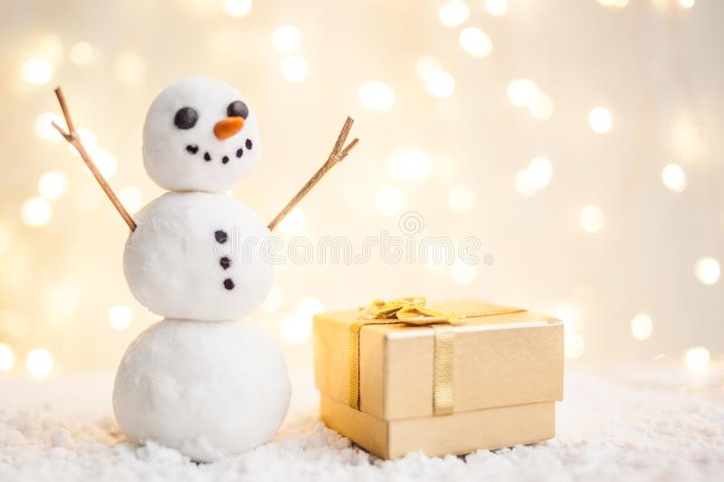 Gift card with a new year and christmas with a picture of a snowman with a sleigh against a backdrop of glowing garlands.  stock photo