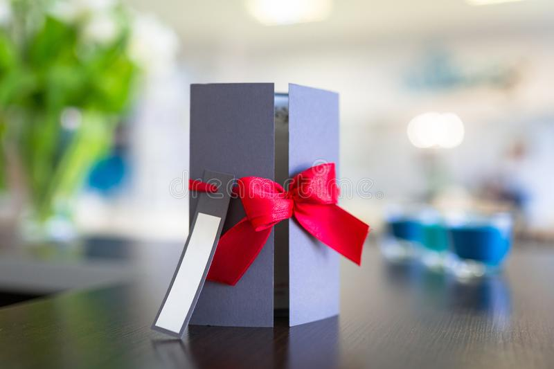 Gift card with red ribbon. On the table stock images
