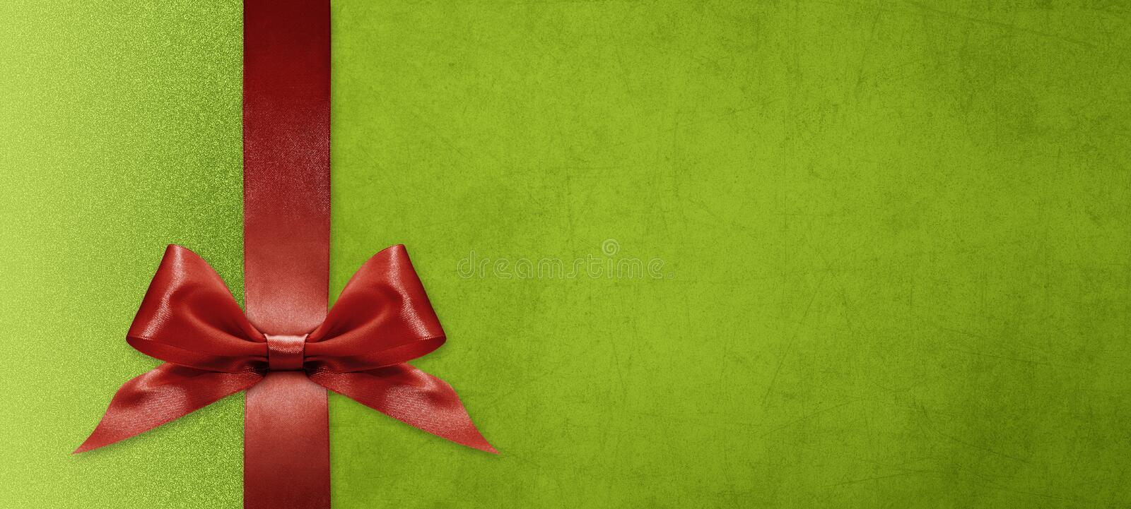 Gift card wishes merry christmas background with red ribbon bow on green shiny vibrant color texture template with blank copy royalty free stock images