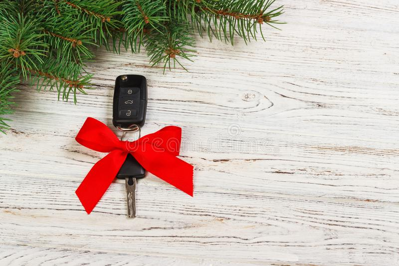Gift for christmas car keys. Close-up view of car keys with red bow as present on wooden background royalty free stock images