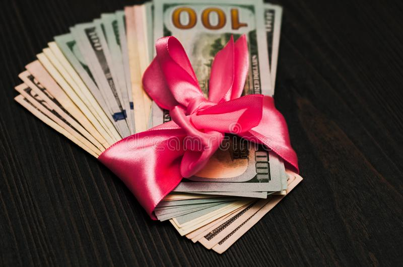 A gift for a Christmas tree. A lot of cash in the bow. stock photos