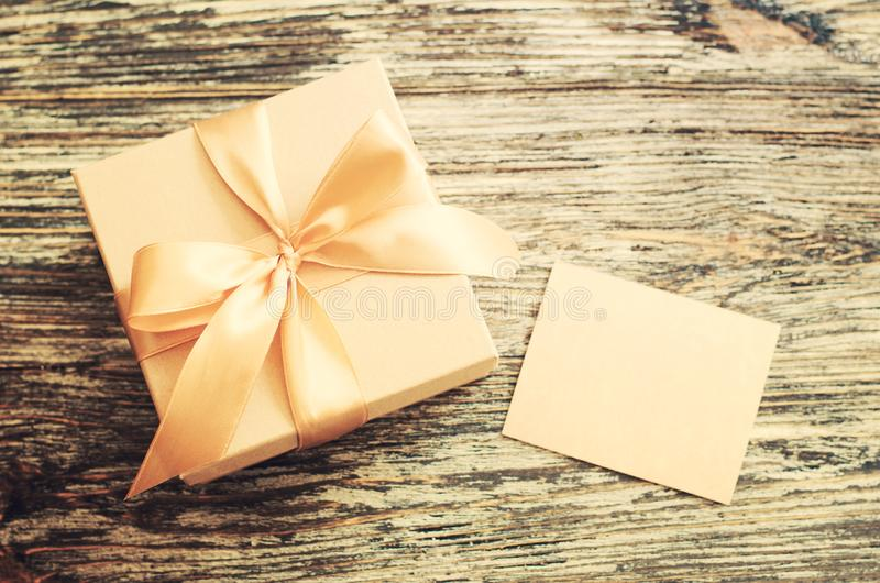 Gift craft paper box with bow ribbon and blank tag stock images