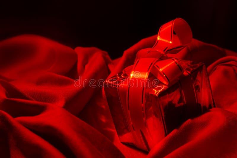 Gift in de dag van de intimiteitsvalentijnskaart in de rode stof van het bladbed Rode gi stock fotografie