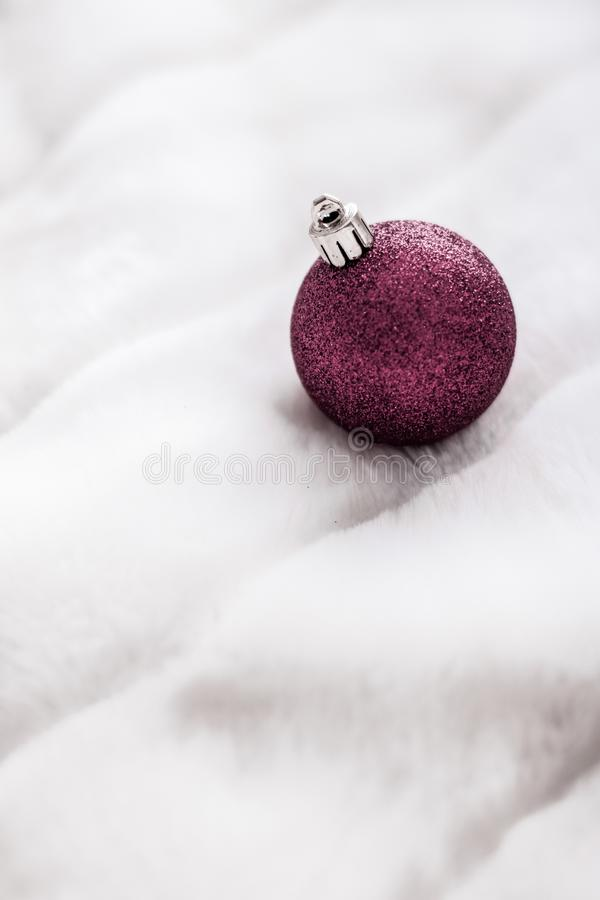 Purple Christmas baubles on white fluffy fur backdrop, luxury winter holiday design background. Gift decor, New Years Eve and happy celebration concept - Purple royalty free stock photography