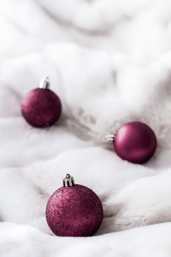 Purple Christmas baubles on white fluffy fur backdrop, luxury winter holiday design background. Gift decor, New Years Eve and happy celebration concept - Purple stock images