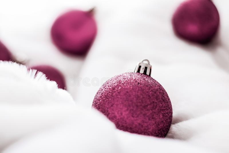 Purple Christmas baubles on white fluffy fur backdrop, luxury winter holiday design background royalty free stock images